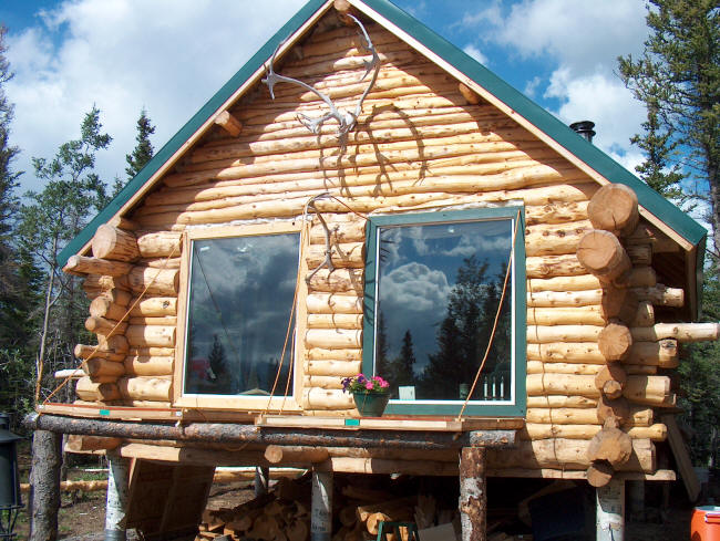 Building a log cabin in alaska the porch and cabinets for Log cabin window trim